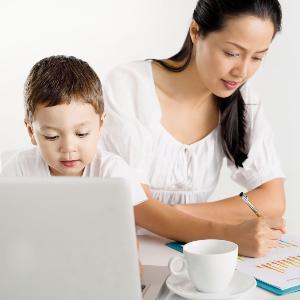 Asiatin mit Kind vor dem Laptop