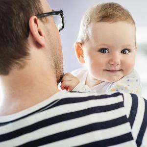 Ein Vater mit Baby auf dem Arm.