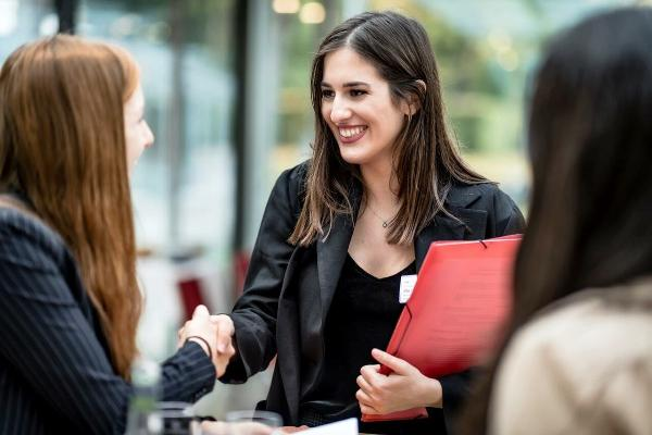 Eine Frau mit einer Bewerbungsmappe in der Hand führt ein Gespräch.