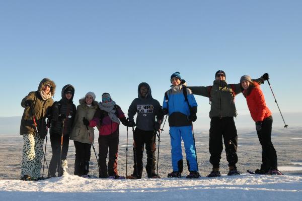 Eine Gruppe von Erasmus-Studierenden mit Schneeschuhen auf einem Hügel in Finnland