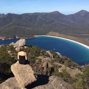 Eine Studentin sitzt auf einem Fels und blickt auf eine Bucht in Australien