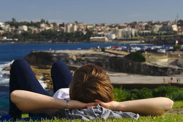 Ein Student entspannt auf einer Wiese in Australien mit Blick auf das Meer.