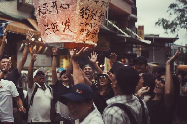 Eine Gruppe von Leuten in Taiwan lässt einen Lampion in die Luft steigen.