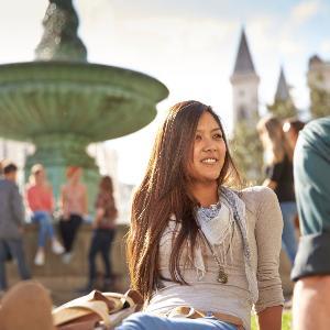 Personen unterhalten sich vor einem Brunnen in einer grünen Wiese sitzend.