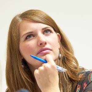 Konzentrierte Studierende hören einem Vortrag zu.
