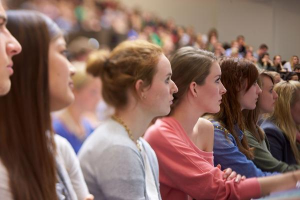 Studentinnen sitzen konzentriert bei einer Vorlesung nebeneinander.