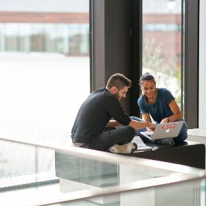 Studierende unterhalten sich vor einem Laptop.