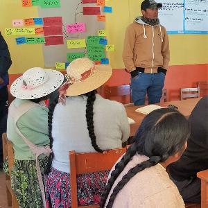 Aufnahme von Menschen in einem Raum in Peru, die sich einen Vortrag anhören.