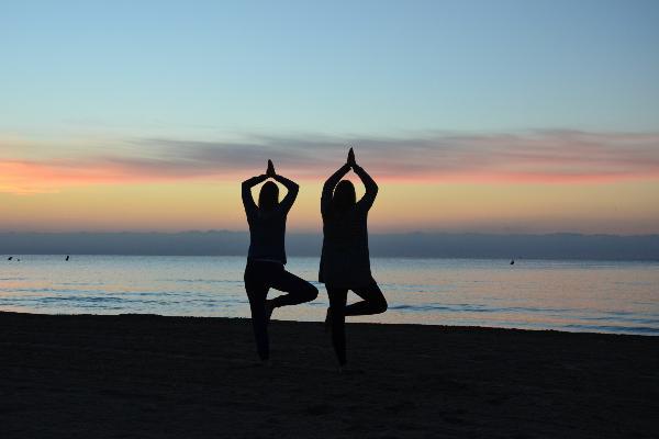 Zwei Studentinnen machen eine Yogafigur an einem Strand vor einem Sonnenuntergang.