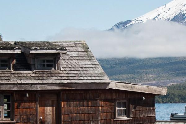 Ein Häuschen auf dem Wasser und im Hintergrund ein Berg, fotografiert in Chile.