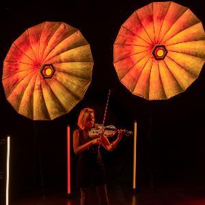 Geige spielende Musikerin vor stylischen Scheinwerfern