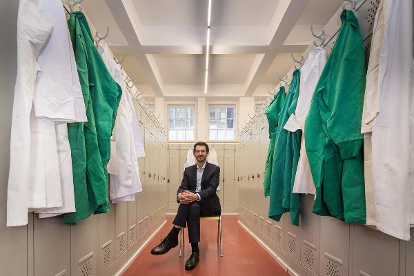 Mann sitzt im Labor Umkleideraum