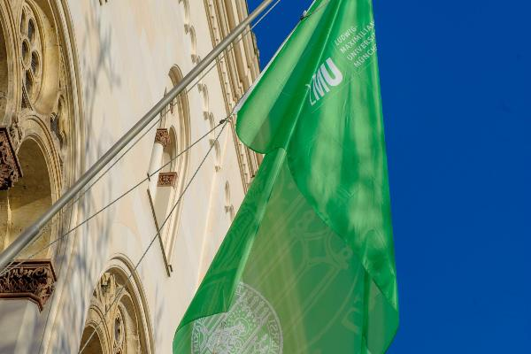 Grüne Flagge mit LMU-Siegel hängt am LMU Hauptgebäude