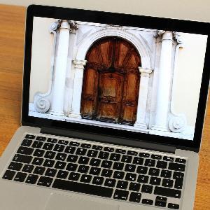 Aufgeklappter Laptop auf dessen Monitor das Foto eines historischen Portals zu sehen ist.