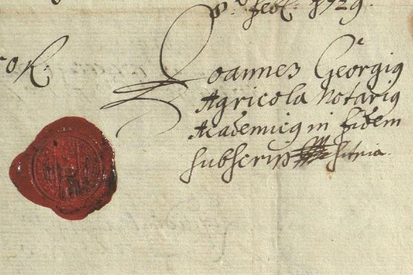 Zu sehen ist der Ausschnitt aus einer historischen Urkunde von 1729 mit dem Universitätssiegel auf rotem Siegellack und der Unterschrift des Universitätsnotars Johann Georg Agricola