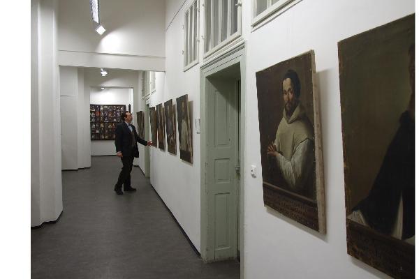 Blick in die UniGalerie, an den Wänden die Exponate der Sonderausstellung, davor der Leiter der UniGalerie, Markus Sattler
