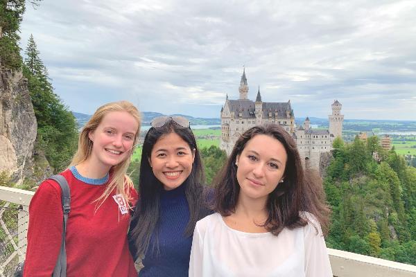 """Drei Teilnehmerinnen der """"Munich International Summer University"""" lächeln in die Kamera. Im Hintergrund ist Schloss Neuschwanstein zu sehen."""