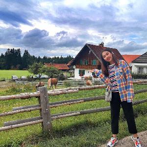 """Eine Teilnehmerin der """"Munich International Summer University"""" steht vor einer Pferdekoppel auf einem bayerischen Bauernhof."""