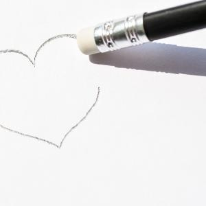 A heart drawn in pencil on paper is erased