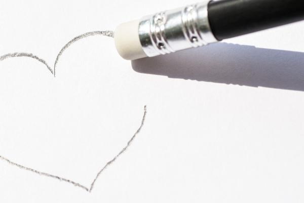 Ein mit Bleistift auf Papier gezeichnetes Herz wird ausradiert