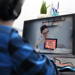 Studierender sitzt vor dem Rechner und nimmt an einer Online-Vorlesung teil.