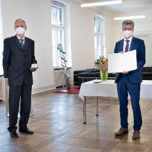 Links steht Prof. Soll mit Maske und Verdienstkreuz links und rechts Minister Sibler mit Urkunde im Flur des Wissenschaftsministeriums