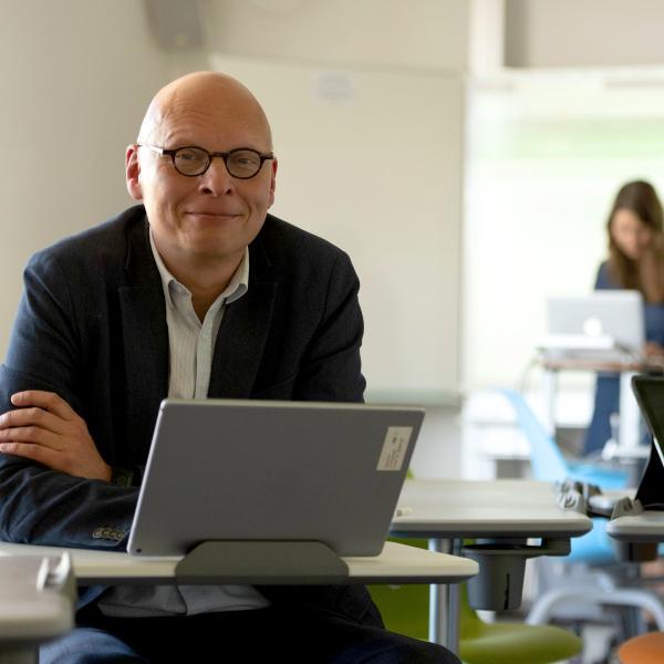 Porträtfoto von Professor Frank Fischer vor einem Laptop in einem Computerraum