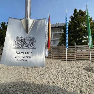 Spaten mit Aufschrift ICON LMU Spatenstich 22.09.2021 steckt im Sand