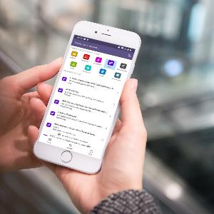 Smartphone in der Hand, auf dem die App der digitalen Ehrenamtskarte zu sehen ist.