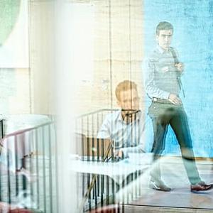 Three people behind a reflecting pane