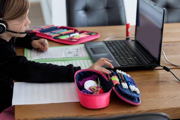 Eine Schülerin sitzt zuhause vor einem Laptop, Schulhefte liegen vor ihr auf dem Tisch