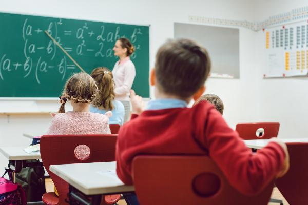Schüler sitzen im Unterricht an ihren Plätzen, die Lehrerin steht erklärend vor der Tafel.