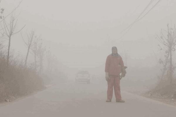 Mann steht kaum sichtbar im Smog