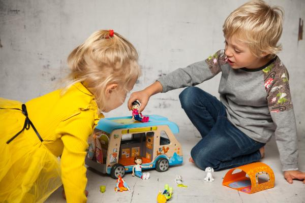 A girl and a boy play with plastic figures