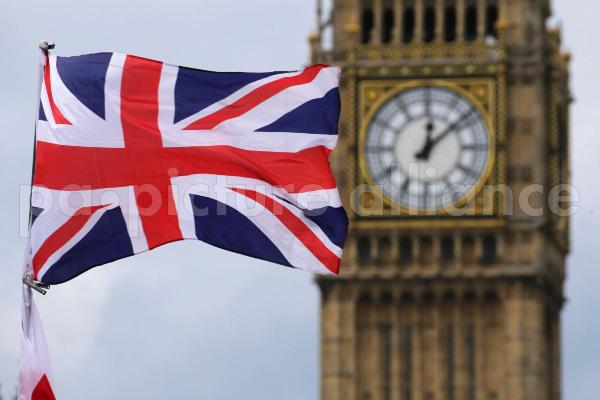A British national flag flies in front of the Big Ben clock tower in London